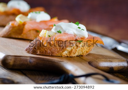 with cream fresh, lemon and chives on wooden background - stock photo
