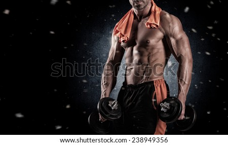 with dumbbells over black background - stock photo