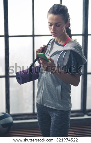 With her yoga mat slung over one shoulder, a fit, healthy woman is standing by the window in her loft gym, casually checking her phone. - stock photo