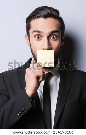 With humor to the deals. Portrait of surprised young man in formalwear covering his mouth with the sticky note while standing against grey background