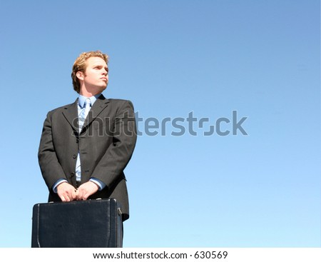 With jaw-jutting determination, a businessman, with both hands on the briefcase, looks to the future