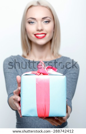 With love. Young smiling blond-haired woman standing on white isolated background and giving present. - stock photo