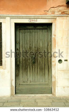 with red-orange wall, ornate green wooden door. - stock photo