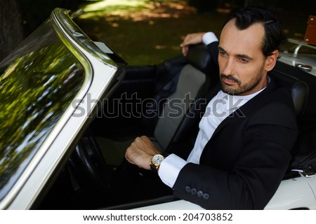 With reflective glance stylish rich man seated in his cabriolet classic car looking away, lifestyle and successful business concept