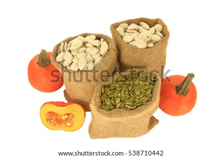 With shell and Hulled (unshelled) Pumpkin seeds in burlap bags (sacks), spherical  pumpkins and half pumpkin with visible seeds over white background