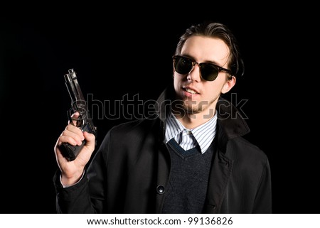 With the haughty grin man in a raincoat with a gun. - stock photo