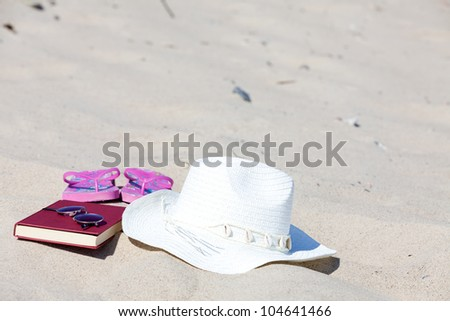 With the straw hat and a book on the beach - stock photo