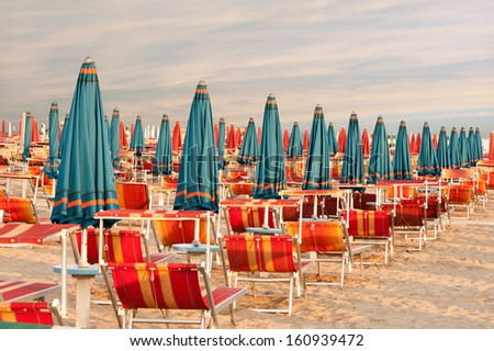 Withdrawn blue umbrellas and red sunlongers on the sandy beach in Italy - stock photo