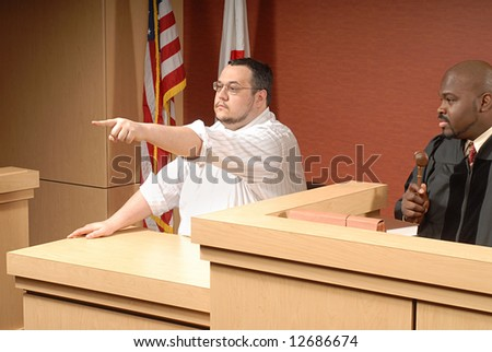 Witness confidently pointing out someone in the courtroom - stock photo