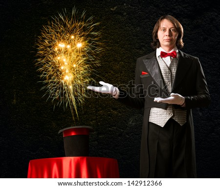 wizard casts a spell over his hat from the hat off smoke, colored lights and magic - stock photo