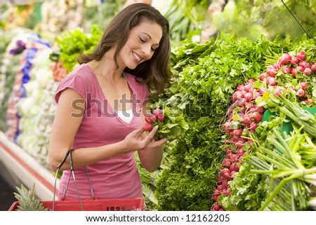 Woamn shopping in produce section of supermarket - stock photo
