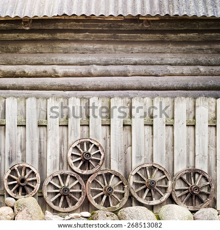 wodden fence near the round log wall, lot of wodden weels and stones near the fence - stock photo