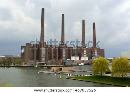 WOLFSBURG, GERMANY - APRIL 15, 2016. View of Volkwagen factory in Wolfsburg, across railroad tracks, with VW logo, vegetation, on a cloudy spring day.
