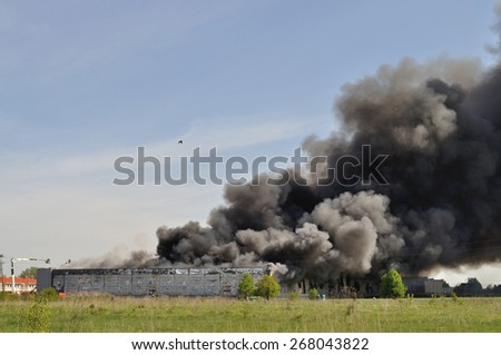 WOLKA KOSOWSKA, POLAND - MAY 10: A cloud of smoke of the burning China Mart storehouse, May 10, 2011 in Wolka Kosowska, Poland. The fire burned 150 storage units covering nearly 2 hectares. - stock photo