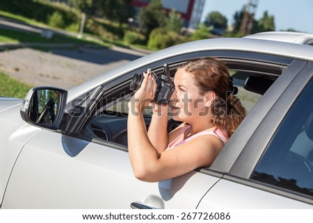 Woman a driver making picture with slr camera while leaning out the car window - stock photo