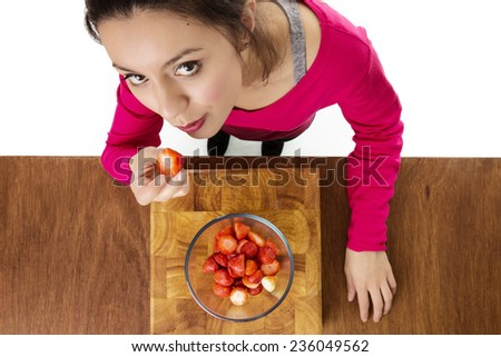 woman about to eat strawberries taken from a birds eye view above looking down - stock photo