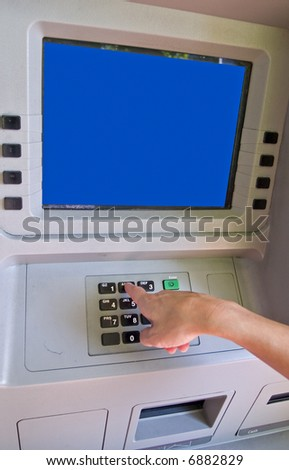 Woman accessing Automatic Teller Machine (ATM) on the street - stock photo