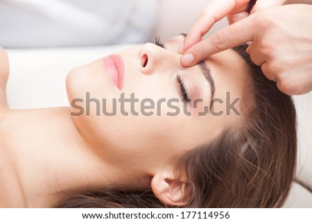 woman acupressure face massage closeup - stock photo