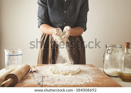 Woman adds some flour to dough on wooden table near knife, two rolling pins, measure cup, transparent jae with flour and olive oil bottle. Step by step cooking pasta dumplings guide - stock photo
