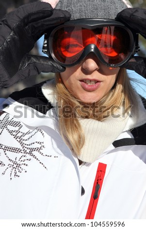 Woman adjusting her ski goggles - stock photo