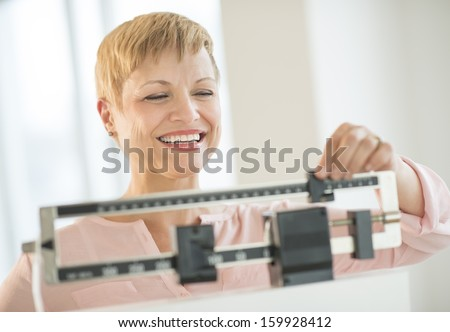 Woman adjusting sliding weight scale - stock photo
