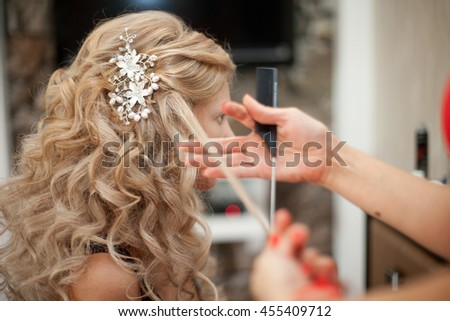 Woman adjusts lady's white curls