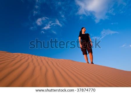 Woman admiring Coral Pink Sand Dunes State Park in Utah - stock photo