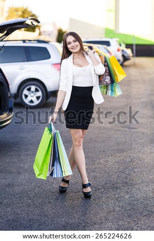 Woman after shopping in a mall or shopping centre and driving home now with her car - stock photo
