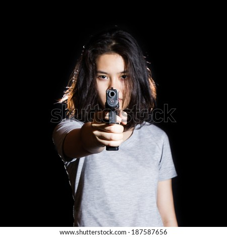 Woman aiming a gun isolated on black background. With focus on the gun.  - stock photo