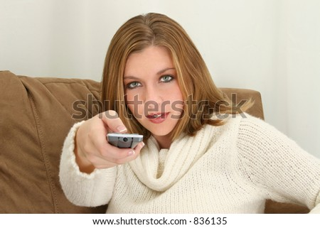 Woman aiming remote control towards camera.  Sitting on couch.  Wearing cream sweater. - stock photo