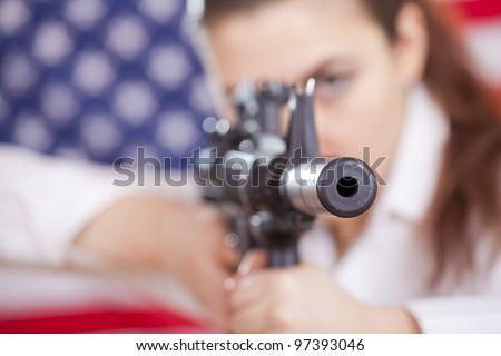 woman aiming with machine gun over american flag - focus on gun barrel - stock photo