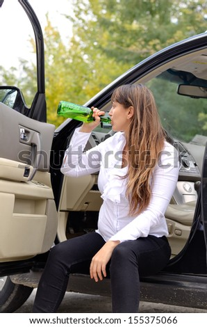 Woman alcoholic drinking while travelling sitting in the open door of her parked car swigging back alcohol from a bottle - stock photo