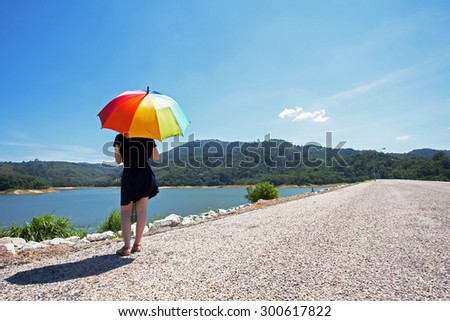 Woman alone color pattern of an umbrella with the sky as background. - stock photo