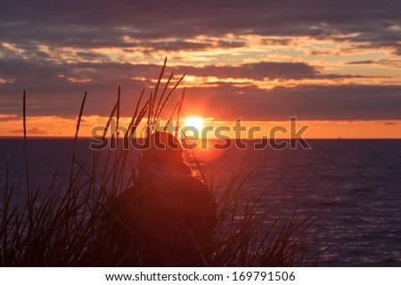 woman alone watching the sea sunset - stock photo