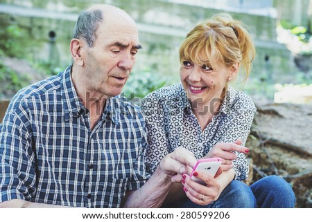 Woman and an old man with a mobile phone  - stock photo