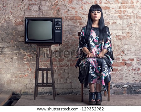 woman and an old television in front of a brick wall. - stock photo