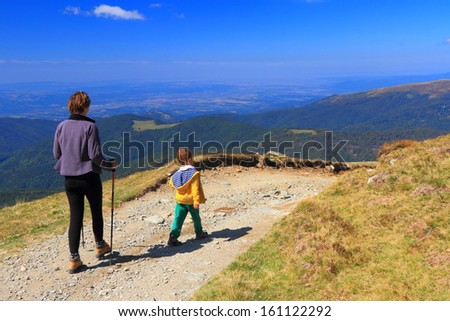 Woman and boy hike on the mountain trail - stock photo