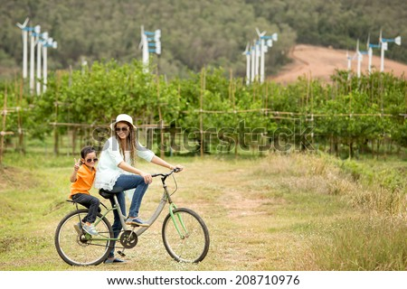 Woman and boy riding bicycle in farm with wind turbines in background