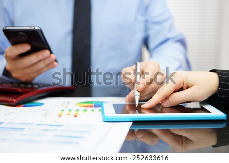 Woman and businessman with mobile phone in hand reviewing report on tablet computer - stock photo