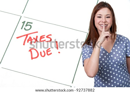 Woman and calendar reminder that Taxes are Due - stock photo
