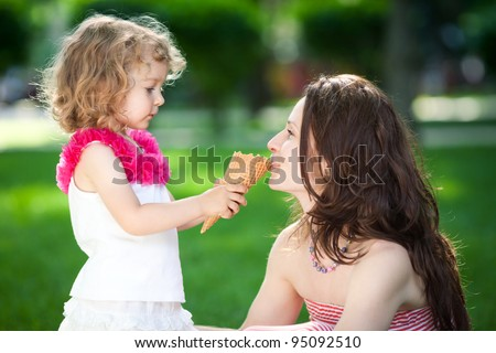 Woman and child eating ice-cream in spring park - stock photo