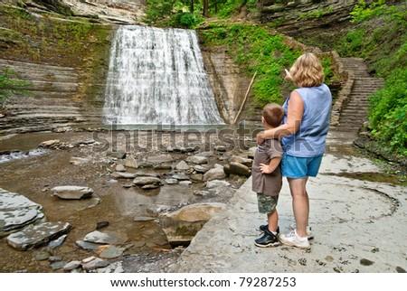Woman and Child Enjoying Waterfall - stock photo