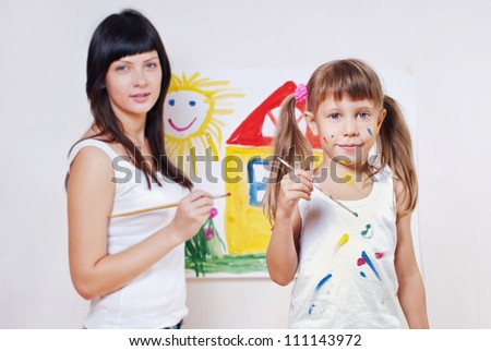 Woman and child have fun paint colors, , focus on the child