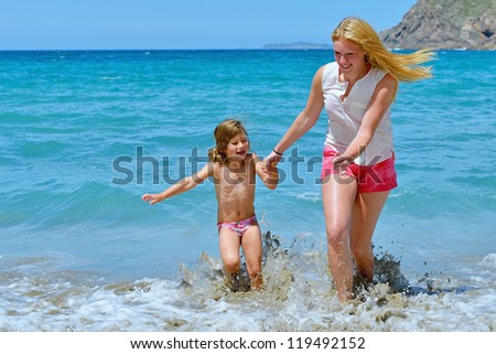 woman and child having fun on the beach - stock photo
