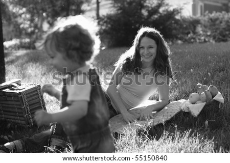 Woman and child having picnic in park - black and white, shallow depth of field - stock photo