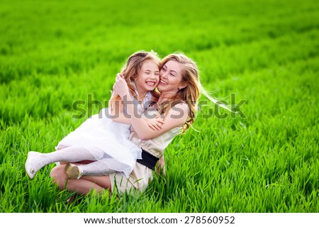 Woman and child playing hide and seek in summer field - stock photo