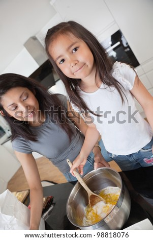 Woman and child preparing dough in kitchen - stock photo