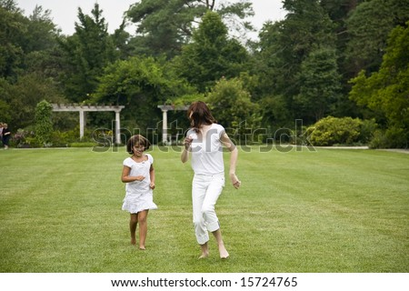 Woman and child running in grass at park