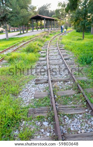 Woman and child walking on train tracks - stock photo