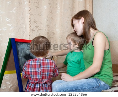 Woman and children draws on the blackboard with chalk - stock photo